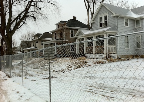 Vintage Dundee homes behind newly erected chain-link fence. All will be demolished, along with the building that housed The 49'r, to make way for a CVS Pharmacy