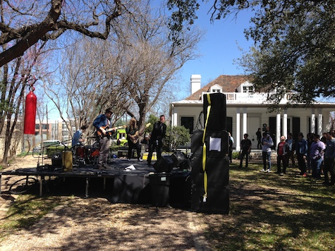A wide shot of the stage and a look at one of the buildings at French Legation Park during Protomartyr's set.